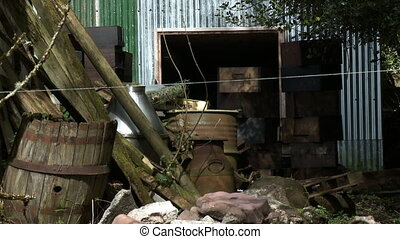 Wide shot of fenceposts, broken barrels, and rocks piled up by a tin shed