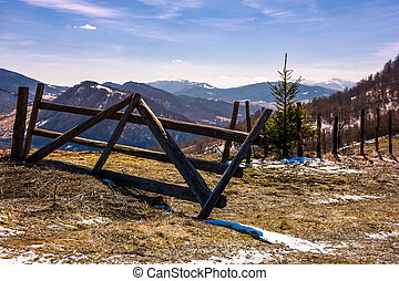 broken wooden fence on hillside. springtime is coming....