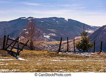 broken wooden fence on hillside. springtime is coming....