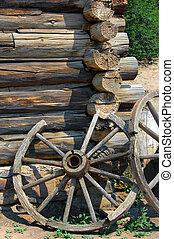 Broken Wooden Spokes - Two rustic wagon wheels lean against...