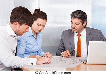 Broker Explaining To Young Couple