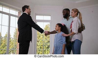 Broker giving house keys to happy little homeowner