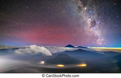 Bromo volcano with milky way, the moon and sand strom ...