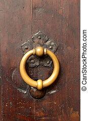 Bronze metal antique vintage door knock or knocker on an old wood door