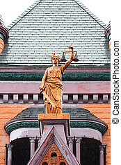 Bronze Statue Holding Scales of Justice and Sword on Historic Building Rooftop.