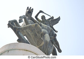 Bronze statue shot from below with sky background