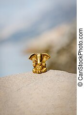 Bronze statuette of the Indian god Ganesha on nature background