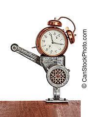 Bronze vintage alarm clock in meat grinder.