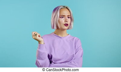 Brooding serious girl with violet hair showing eureka ...