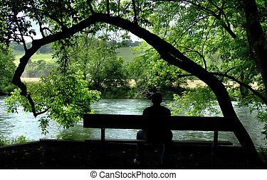 Brooding Thoughts - Young man sits on the banks of a river ...