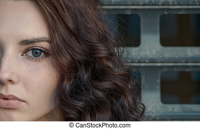 Broody girl half face in front of metal grid looking at...