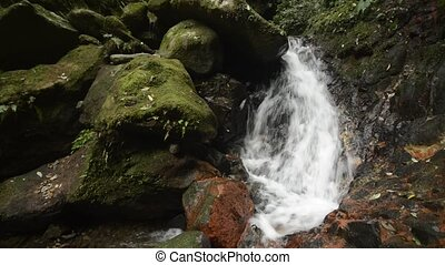 Brook beside mossy stones - Fast brook flowing on rock slope...