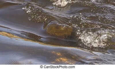 Closeup of fast flowing water. - Brook water flows through...