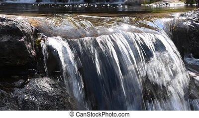 Brook or river running water stream flow with small rift over the stone shelf in bright sunny day time, diagonal, low angle view, close up