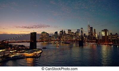Panoramic view of Brooklyn bridge and Manhattan at night, New York City.