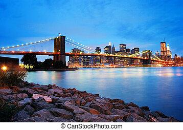 Brooklyn Bridge and Manhattan skyline in New York City over...