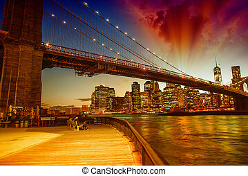 Brooklyn Bridge at dusk with Manhattan skyline, beautiful sky colors.