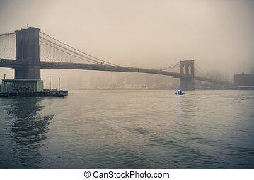 Brooklyn bridge at foggy evening