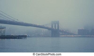 Brooklyn bridge at foggy morning, New York City.