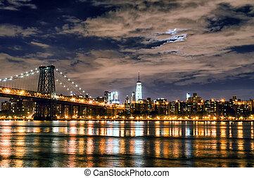 Brooklyn Bridge over East River at night.