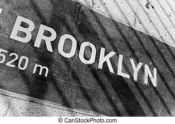 A sign that reads BROOKLYN on a placard mounted in the concrete. You can see the shadows from the bridges wires.
