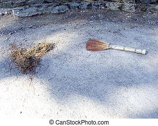 Broom and dust on sidewalk