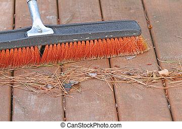 Broom sweeping outdoor deck - Large broom sweeping pine tree...
