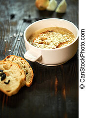 Broth with toasts of bread and black olives