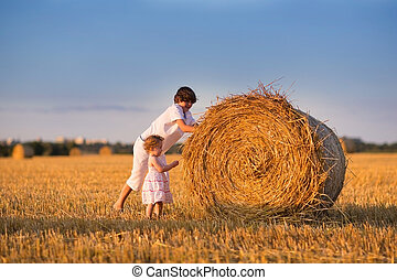 Brother and baby sister pushing hay bales in a field at...