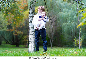 Brother and baby sister walking in a park