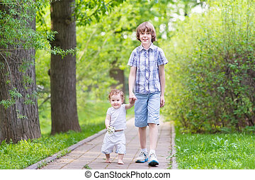 Brother and baby sister walking in the park