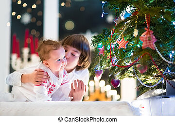 Brother and his baby sister playing together at a Christmas tree
