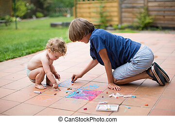 Brother and his baby sister playing together in the backyard pai