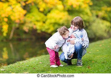 Brother and his little toddler sister comforting and kissing the