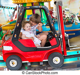 Brother and little baby sister enjoying a ride in an...