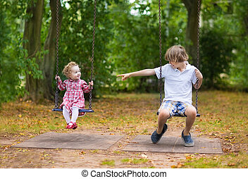 Brother and little baby sister playing together on a swing on a