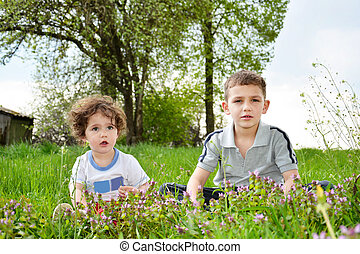 Brother and little sister sitting in flowers.