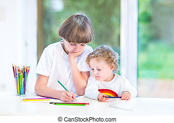 Brother and little toddler sister having fun together painting a