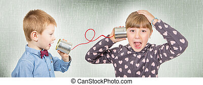 brother and sister are talking with tin can telephone