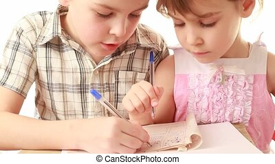 Brother and sister draw something in notebook