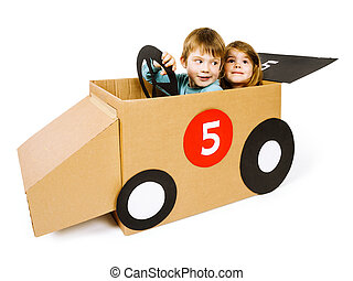 Brother and sister driving a cardboard car