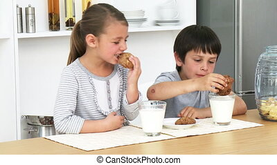 Brother and sister eating biscuits with milk - Little...