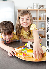 Brother and sister eating cookies in the kitchen