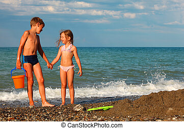 brother and sister hold hands and stand on beach. boy holding plastic orange bucket