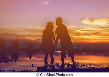 Brother and sister holding hands together with sun set.
