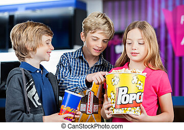 Brother And Sister Holding Snacks At Cinema