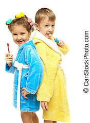 Brother and sister in blue and yellow dressing gown brush their teeth on white background. Close-up. Isolated.