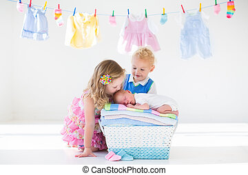 Brother and sister kissing newborn baby - Newborn child on a...