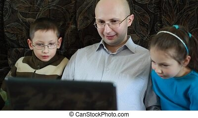 Brother and sister look as father in glasses works on laptop