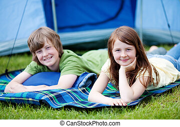 Brother And Sister Lying On Blanket With Tent In Background